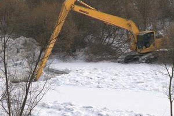Technika v teréne. Snaží sa uvoľniť tok rieky Poprad.