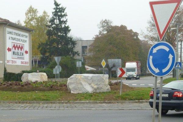 Oproti vstupu do okružnej kižovatky sú dva kamenné bloky.