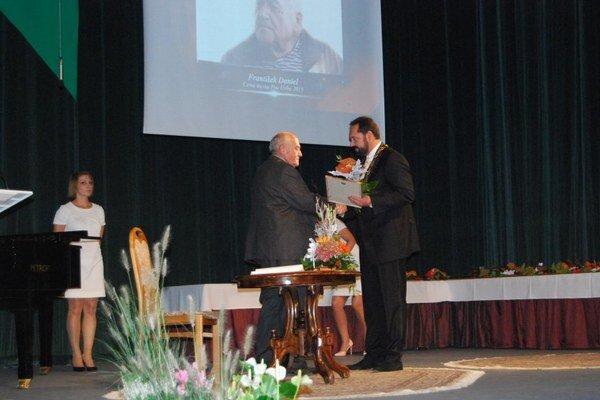 Minuloročné udeľovanie cien. Primátor mesta Nové Zámky odovzdáva cenu Františkovi Danielovi, predsedovi občianskeho združenia Za troma mostami.