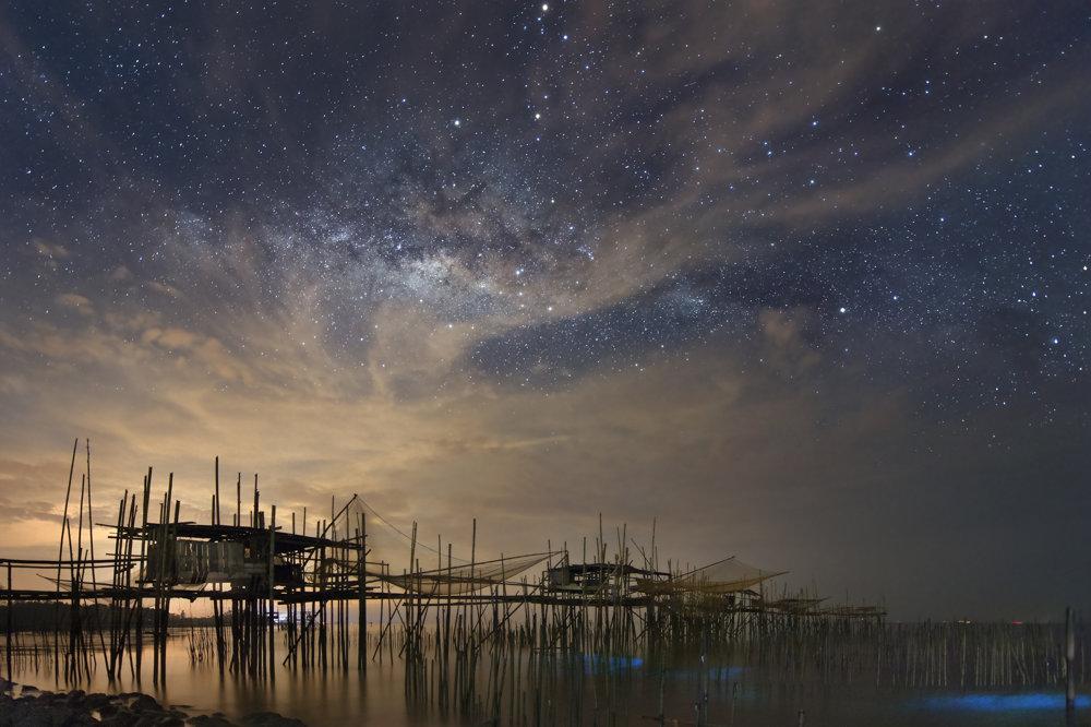 Prirodzené svetlo nočnej oblohy a vodnej bioluminescencie bojuje so svetelným smogom nad Malajziskou rybárskou dedinou. FOTO - Yuyun Wang
