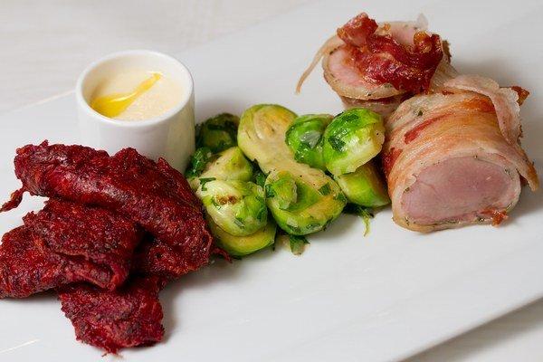 Pečená bravčová panenka v slanine s cviklovo-zemiakovými plackami, ružičkovým kelom a chrenovou omáčkou.