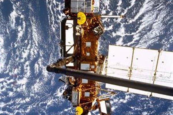 """Družica UARS. V popredí vidno rameno robotického manipulátora, ktorý družicu """"vyložil"""" z raketoplánu Discovery do vesmíru."""