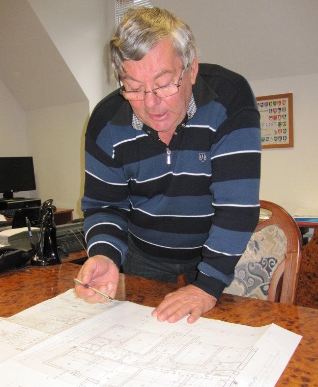 Starosta Štefan Závadinka ukazuje pôvodné plány na výstavbu nájomných bytov.