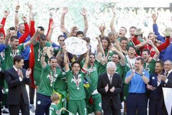 Majstri. Hráč Wolfsburgu Josue (uprostred) drží trofej po zisku ich prvého bundesligového titulu. Na snímke vľavo hore slovenský futbalový obranca Peter Pekarík.
