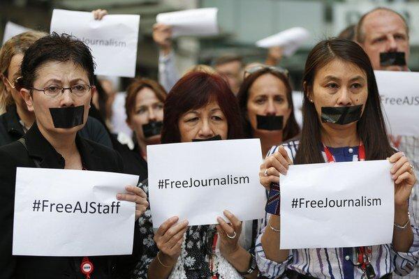 Novinári a zamestnanci  britskej rozhlasovej a televíznej spoločnosti BBC s čiernymi páskami na ústach držia minútu ticha na podporu uväznených novinárov 24. júna 2014.