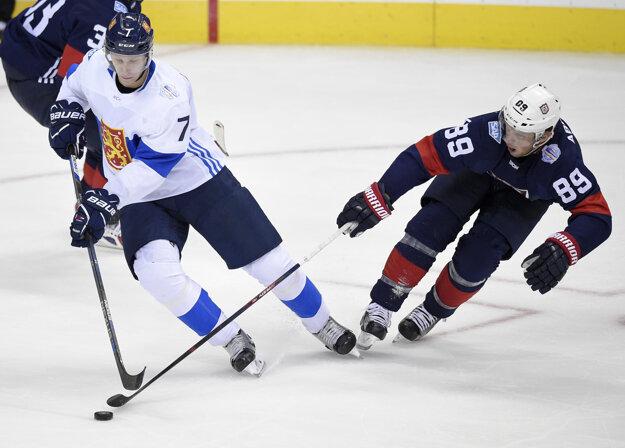 Fínsky hokejista Esa Lindell (vľavo) sa pokúša dostať cez Američana Justina Abdekladera.