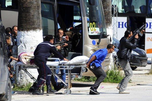 Príslušníci tuniských bezpečnostných síl kryjú streľbou záchranárov, ktorí prevážajú zraneného počas akcie v múzeu Bárdú v Tunise 18. marca 2015.