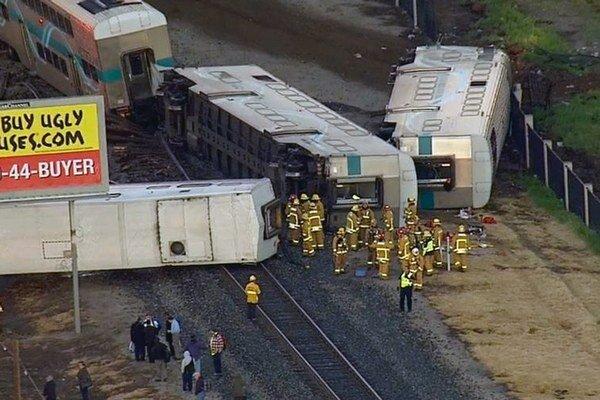 Hasiči stoja pri vraku osobného vlaku Metrolink, ktorý sa vykoľajil počas jazdy na železnici v kalifornskom meste Oxnard.