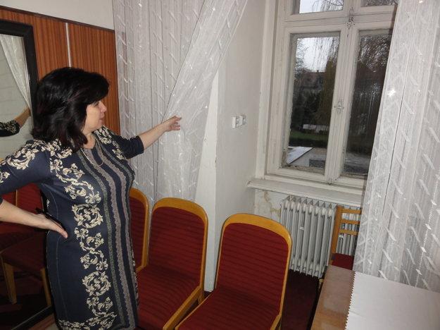 Okná na kaštieli sú v dezolátnom stave. Ukazuje ich Klaudia Ivanovičová z Mestského strediska kultúry a športu, ktoré v kaštieli sídli.