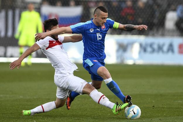 Kapitán slovenskej dvadsaťjednotky Adam Zreľák (vpravo) bojuje o loptu s Turkom Hakanom Cinemrem počas prvého vzájomného zápasu v marci 2016. Teraz Zreľák pre zranenie hrať nebude.
