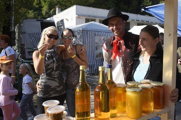 Ľudia stoja pred stánkom včelára počas 20. ročníka Dní ovocia a medu.