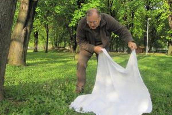 Entomológ mapuje výskyt kliešťov v nitrianskom parku. Prechádza flanelovou látkou po tráve, kliešte, ktoré  sa na látku prichytia, potom pozbiera a spočíta.