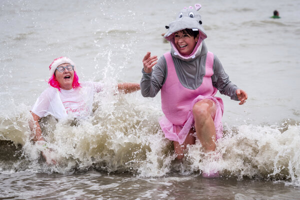 Ľudia sa v bláznivých kostýmoch zúčastňujú na tradičnom novoročnom plávaní v Severnom mori.