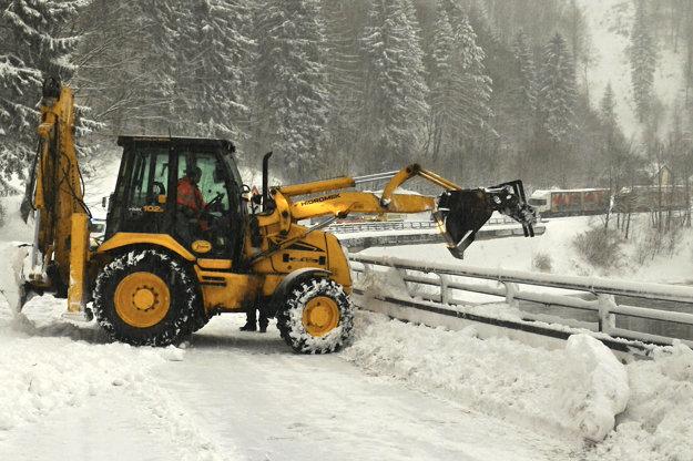Odpratávanie snehu z cestnej komunikácie po páde lavíny v Kraľovanoch.