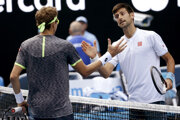 Novak Djokovič (vpravo) si po zápase podáva ruku s Denisom Istominom.