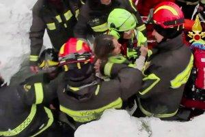 Záchranári vyťahujú z trosiek hotel ženu.