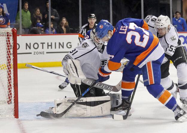 Anders Lee z New Yorku Islanders doráža puk za chrbát brankára Petra Budaja.