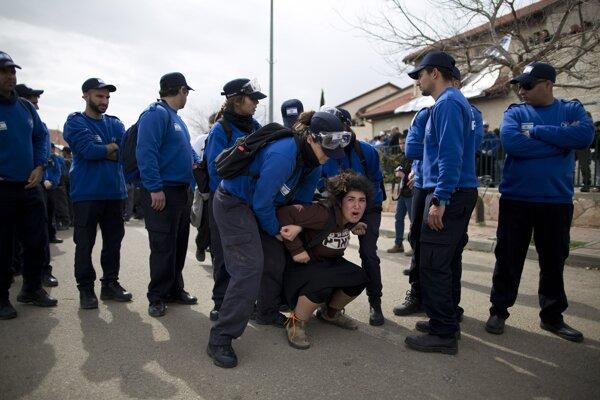 Izraelskí policajti vynášajú osadníčku pri zásahu počas vysťahovania.