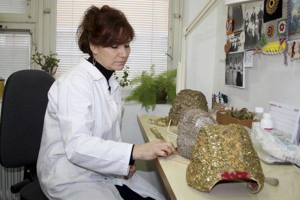 Konzervátorka Anna Vavrová pri čistení čepcov zlatohlavov