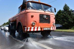 Cisternové vozidlo polieva cestu vodou v Trebišove 6. júla 2015. Mestská samospráva sa snaží zmierniť horúčavy, ktoré sužujú v tomto období celé Slovensko.