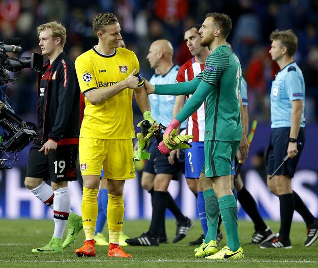Brankár Leverkusenu Bernd Leno (vľavo) blahoželá Janovi Oblakovi z Atlética Madrid.