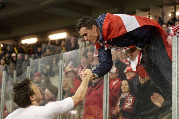 Dánsky futbalista William Kvist si podáva ruku s jedným z fanúšikov.