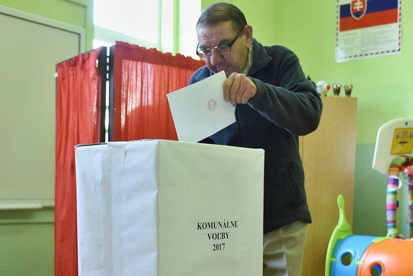 Na snímke muž hádže obálku s volebným lístkom do urny vo volebnej miestnosti v Stráňach pod Tatrami počas nových volieb do orgánov samospráv.