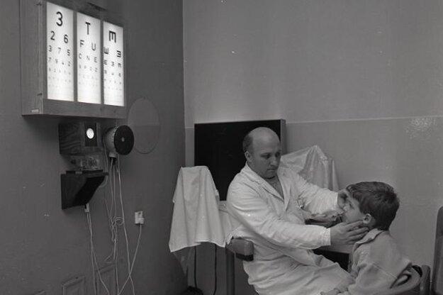 Jozef Javorský meria cez priz-mu uhol škúlenia dieťaťa pomocou zvukovo-svetelného fixačného prístroja.