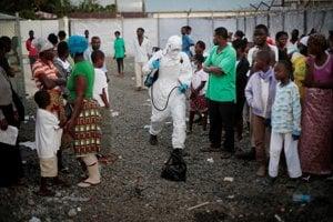 Na snímke z roku 2014 zdravotnícky pracovník postrekuje ľudí pred klinikou na ošetrovanie nakazených ebolou v Monrovii, hlavnom meste Libérie.