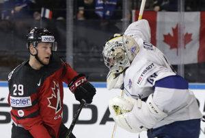 Francúzsky brankár Florian Hardy vyráža puk pred Nathanom MacKinnonom z Kanady.