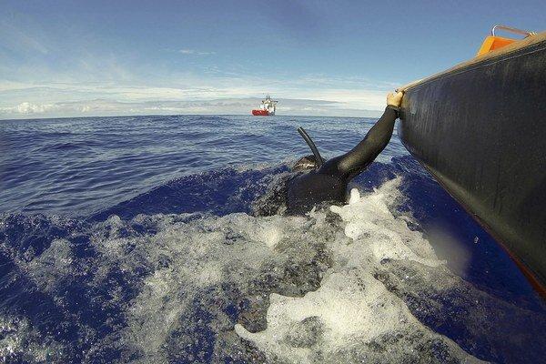 Potápač hľadá trosky zmiznutého lietadla v hlbinách Indického oceána.