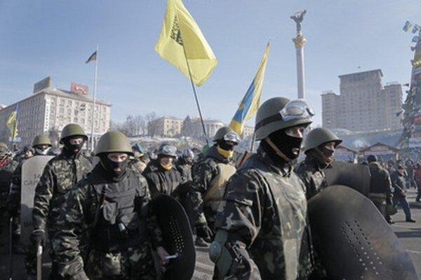 Ukrajinskí demonštranti s palicami na námestí v Kyjeve.
