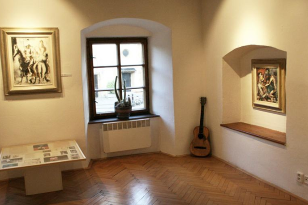 Pohľad do expozície, vktorej je okrem Sokolových diel aj jeho gitara. Okná zdobia kaktusy. Foto: (BEA)