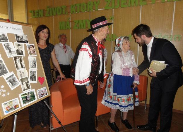 Grácovci prijímajú gratulácie, vľavo panel s fotografiami z ich života.