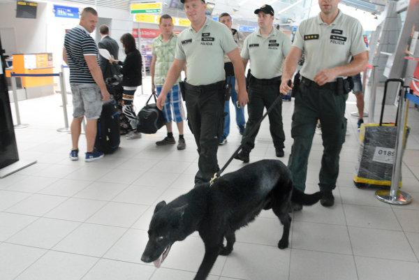 Policajti so psom. Prechádzajú terminál letiska.