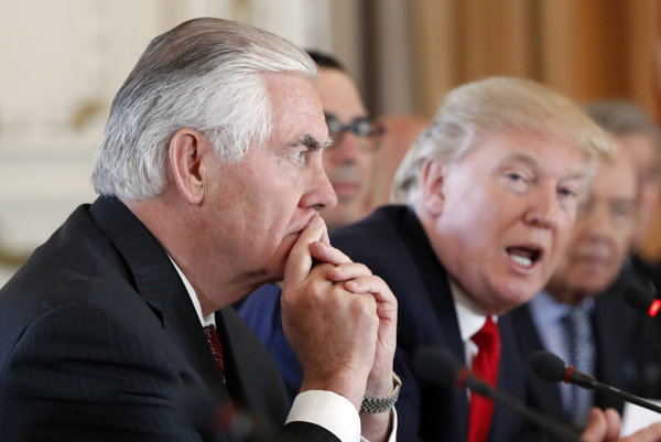 Minister zahraničných vecí USA Rex Tillerson (vľavo) zamyslene sedí, kým prezident Donald Trump rozpráva.