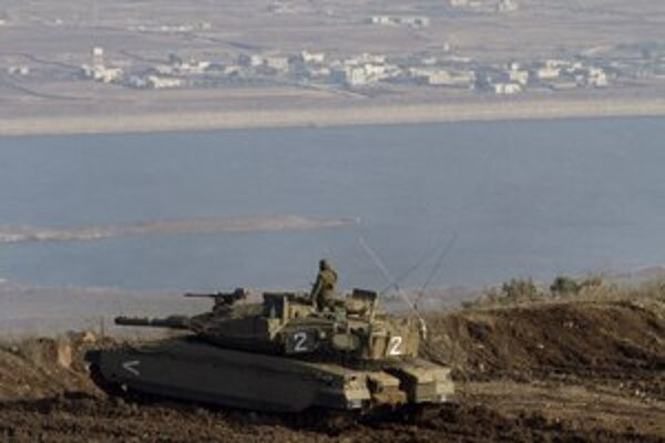 Izraelský vojak z tanku pozoruje sýrsku dedinu pri hraniciach na Golanských výšinách.