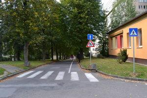 Pri hlavnej budove. Kedysi pozdĺž cesty parkovali vozidlá, dnes je tam už vyhradený chodník pre chodcov.