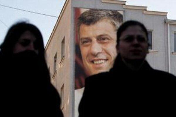 Kosovčanky prechádzajú pred billboardom s portrétom premiéra Hašima Thaciho na budove jeho Kosovskej demokratickej strany v Prištine.