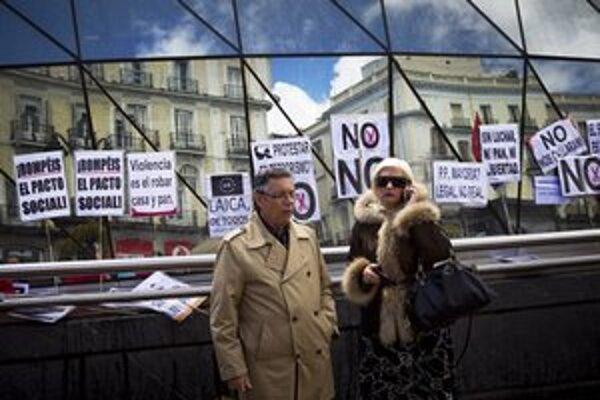 Starší pár pozoruje demonštrantov v Madride.