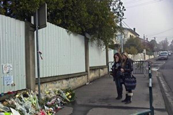 Ľudia nosia k škole kvety a zapaľujú sviečky.