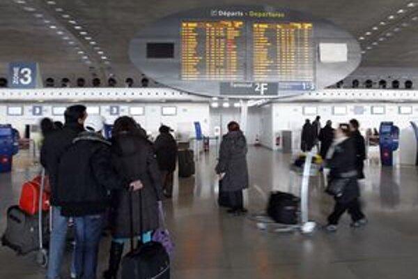 Cestujúci pozerajú na tabuľu odletov na parížskom letisku Charlesa de Gaulla.