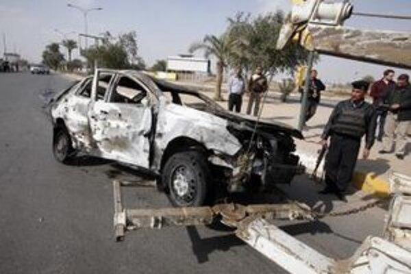 Bezpečnostné sily odnášajú auto, ktoré bolo zničené počas útoku v irackom Bagdade.