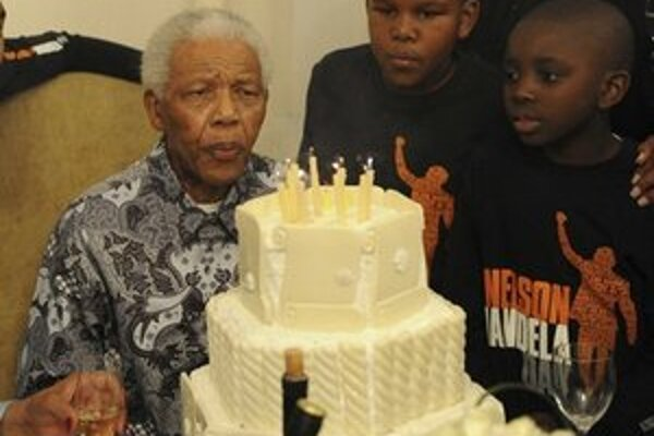 Na archívnej snímke z 18. júla 2010 Nelson Mandela sfukuje sviečky na narodeninovej torte.