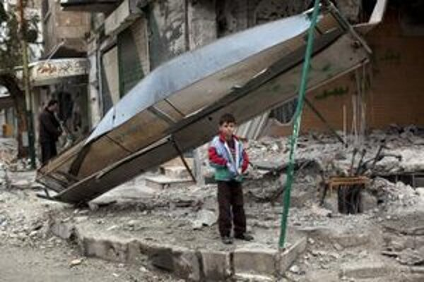 Chlapec stojí pred obchodom, ktorý zničila sýrska armáda na severe krajiny.