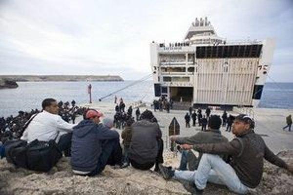 Migranti zo Severnej Afriky, ktorí priplávali loďou na ostrov Lampedusa, čakajú na nalodenie sa na trajekt.