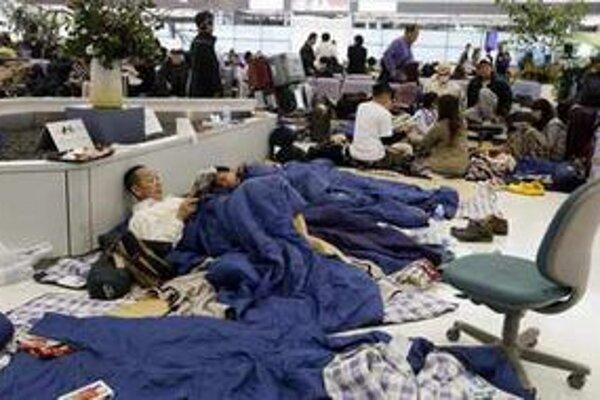 Cestujúci spia na zemi v priestoroch letiska Narita neďaleko Tokia.