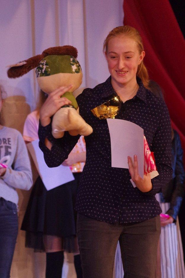Absolútrna víťazka speváckej súťaže. Drobné dievča s trochu chlapčenským výzorom a veľkou silou hlasu.