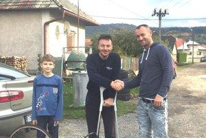 Michal Labat (v strede) pri preberaní handbiku od Miroslava Buľovského (vpravo).