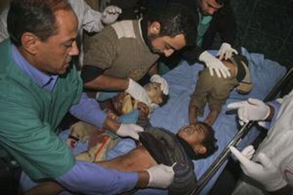 Palestínski zdravotníci ošetrujú deti, ktoré údajne zranila izraelská tanková strela.